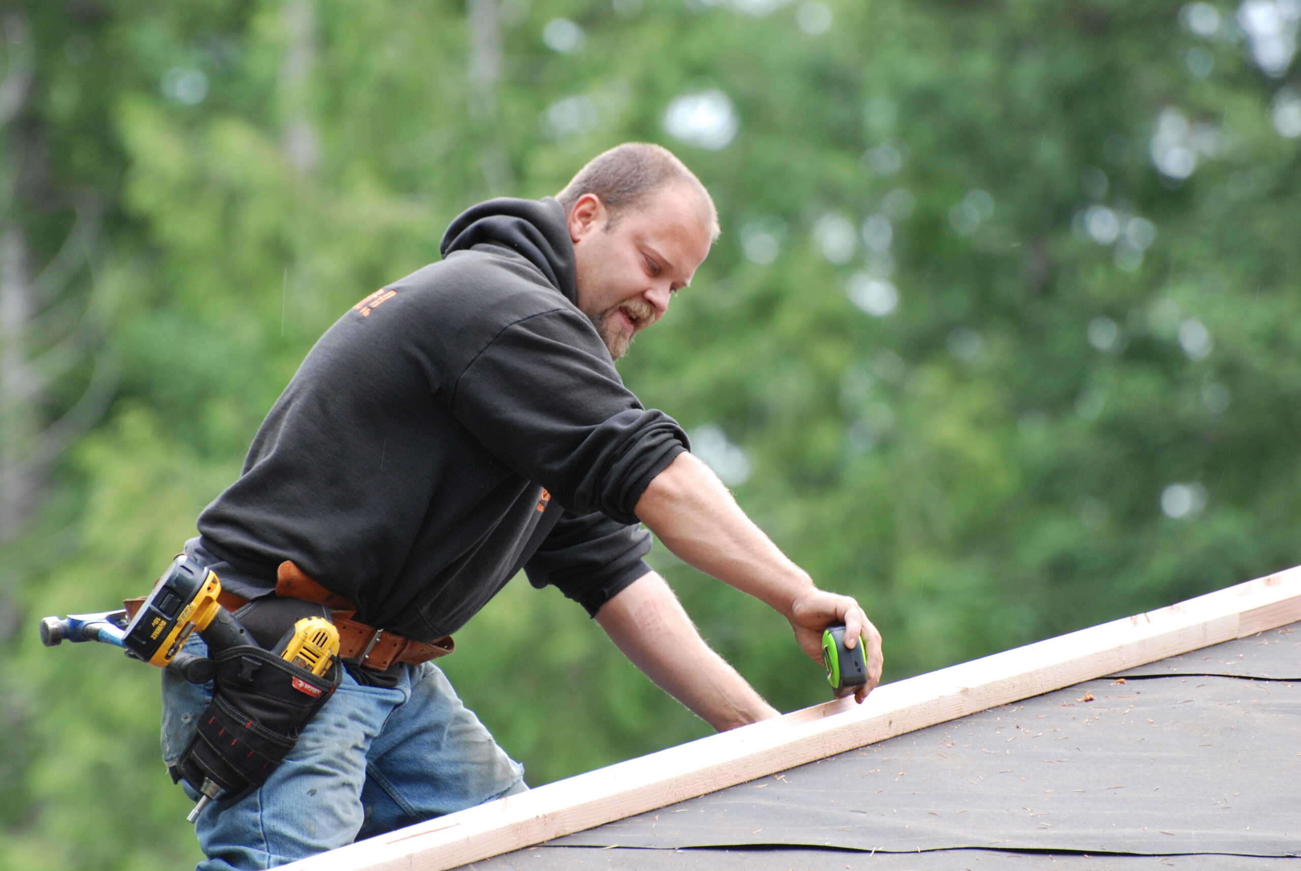 Roofer Taking Measurements of Roof