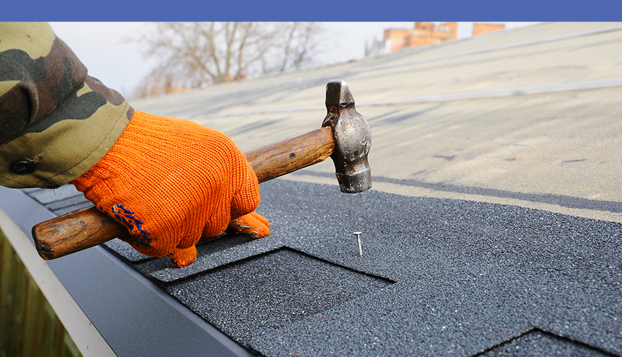 Roofer Using Hammer and Nail